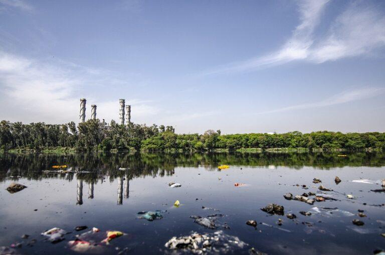 contaminacion del agua de un rio por basura al lado de una fabrica