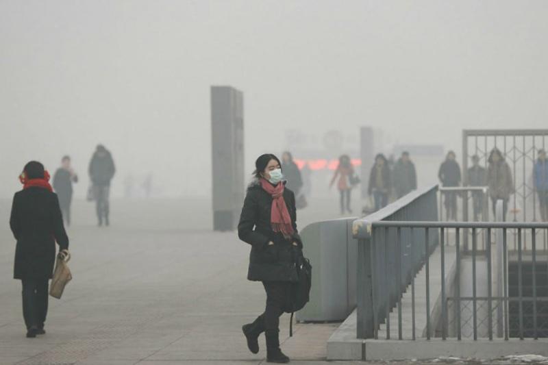 mujer y otras personas caminando con mascarillas en una calle donde hay mucha contaminacion del aire