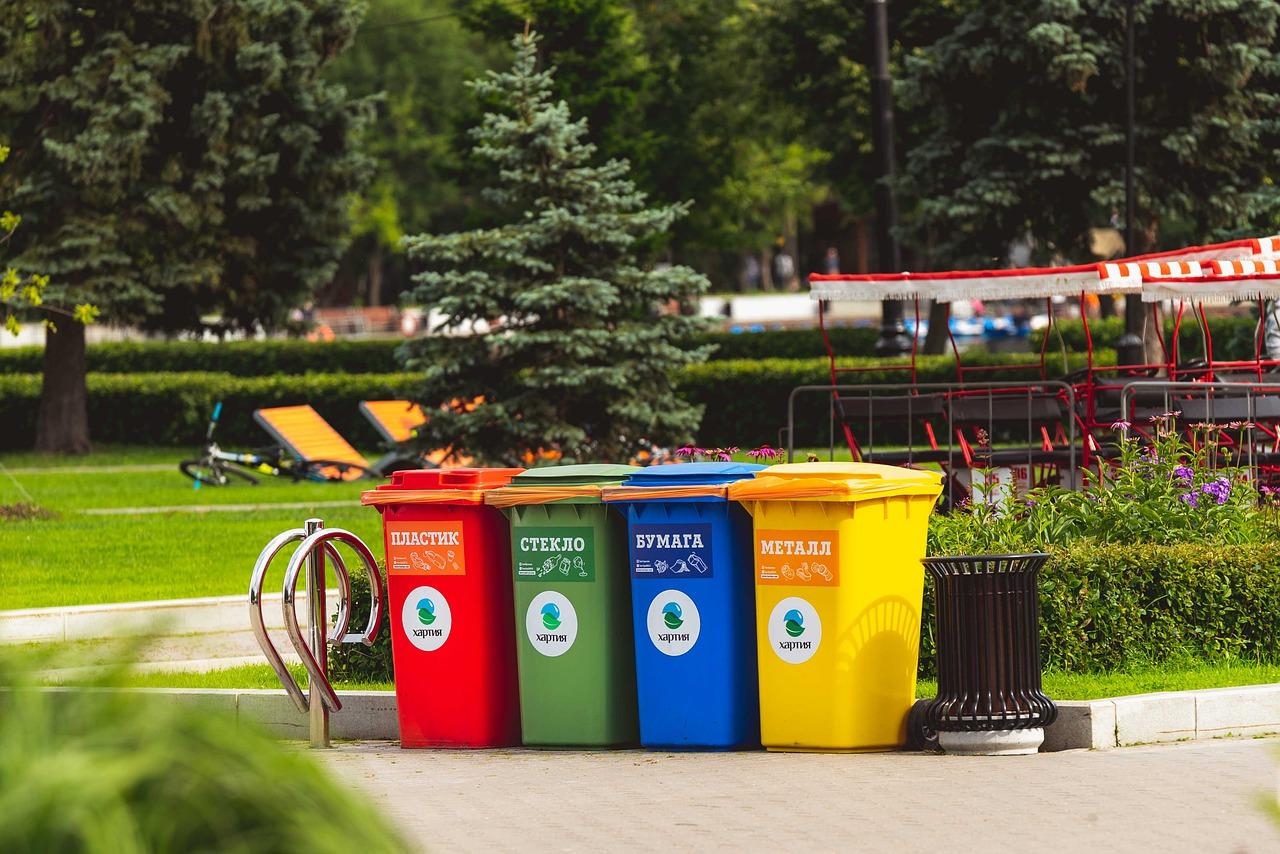 4 botes de reciclaje de colores rojo, verde, azul y amarillo al lado de una caneca regular en un parque