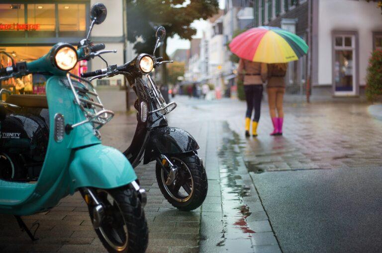 dos scooters electricas y mujeres bajo la lluvia