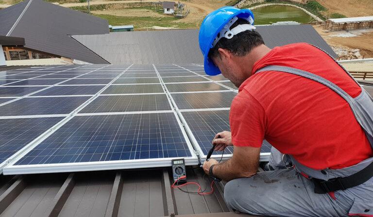 tecnico instalando paneles solares en el techo de una casa