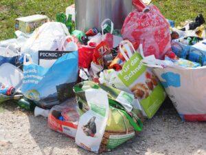 alimentos acumulados al lado de un bote de basura
