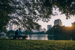 pareja sentada en un parque en la ciudad con arboles y un lago